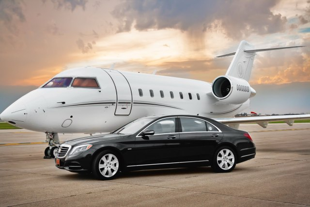 black mercedes s class parked in front of a small white plane