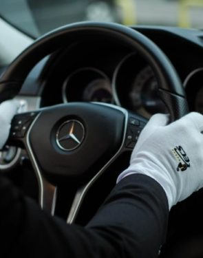 Man holding a mercedes steering wheel in white gloves