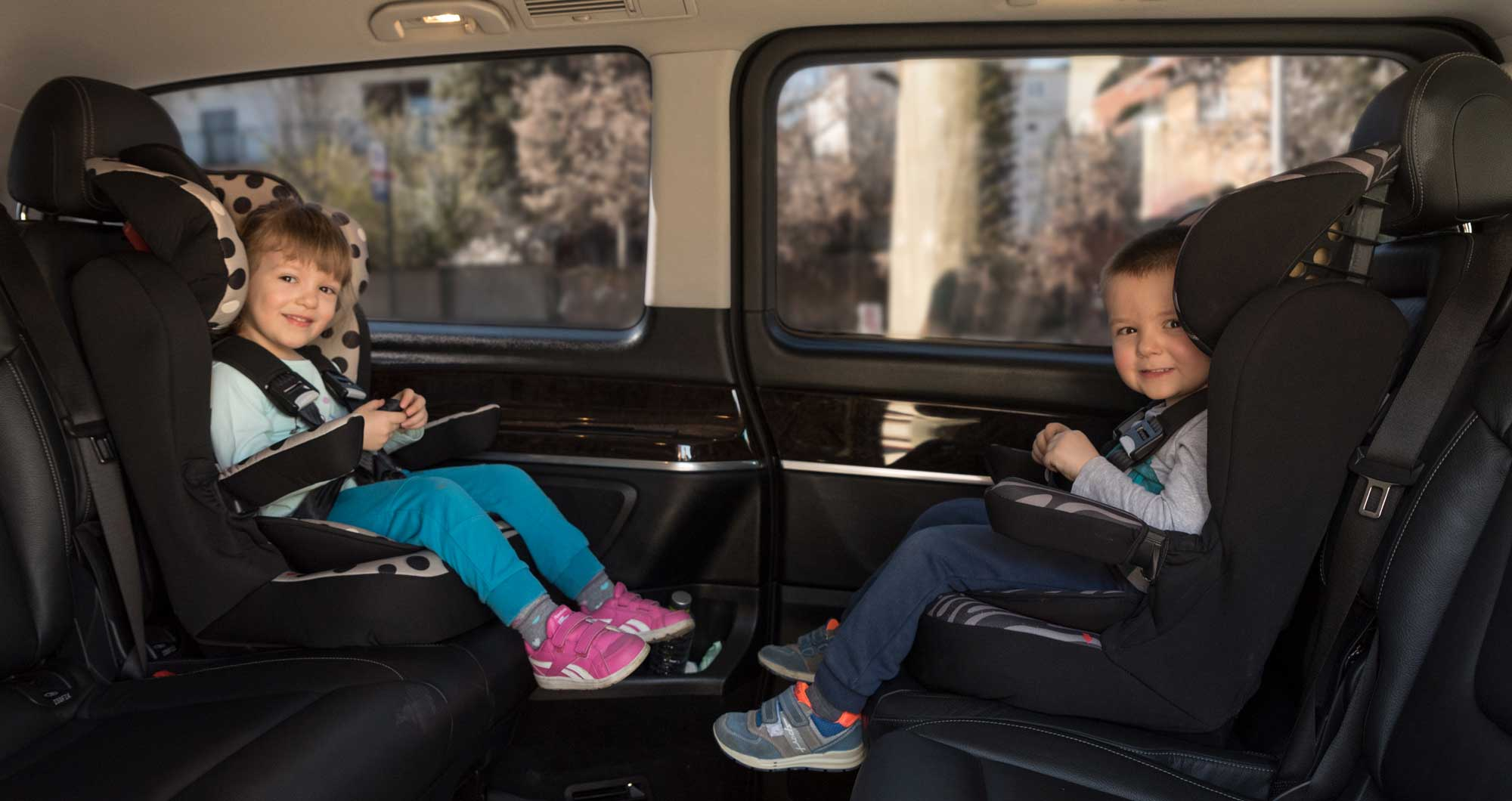 Two kids sitting in the back of the van in their child seats