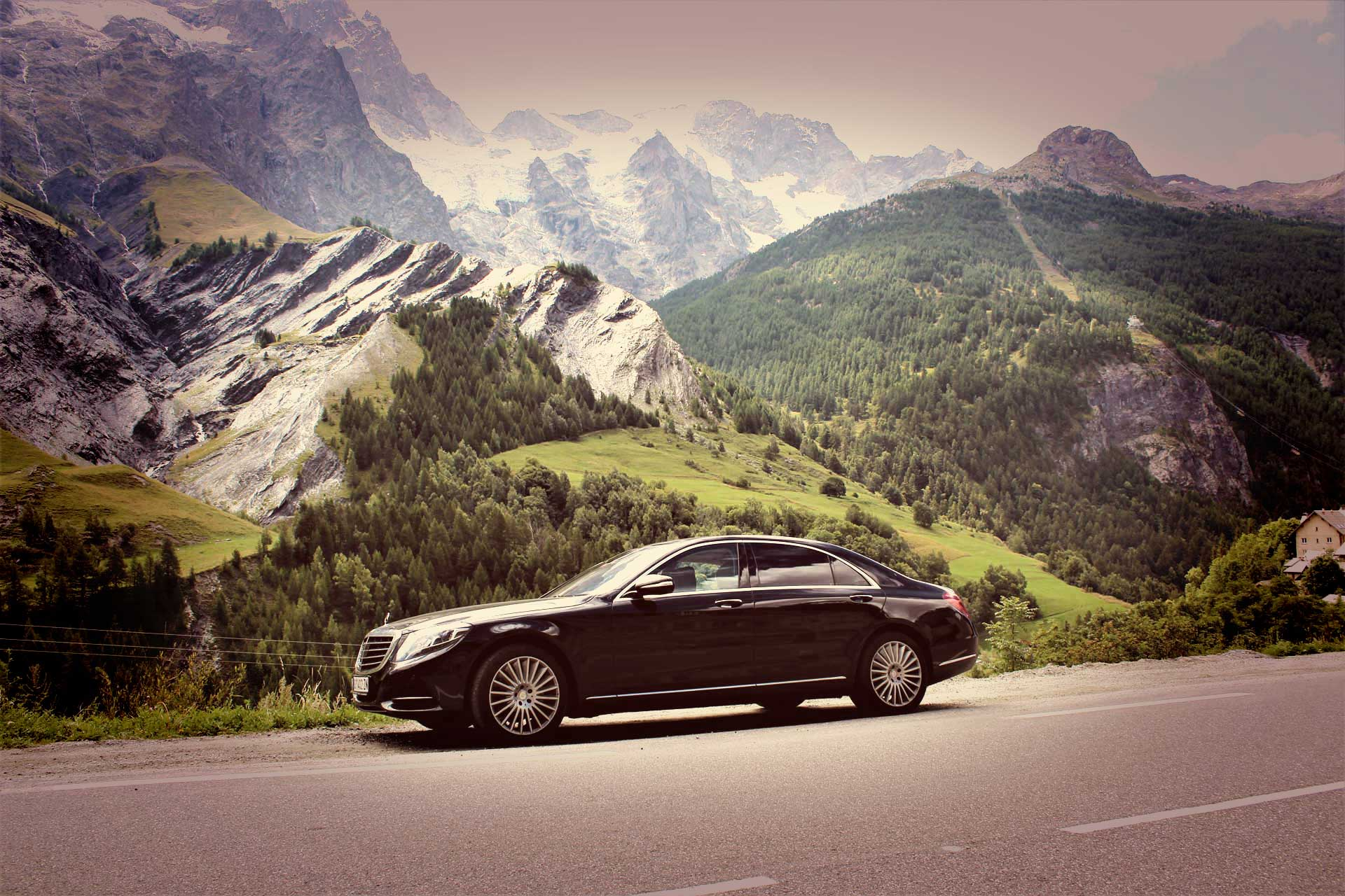 Black Mercedes S class parked besides the road with Alpes mountains behind on the horizon